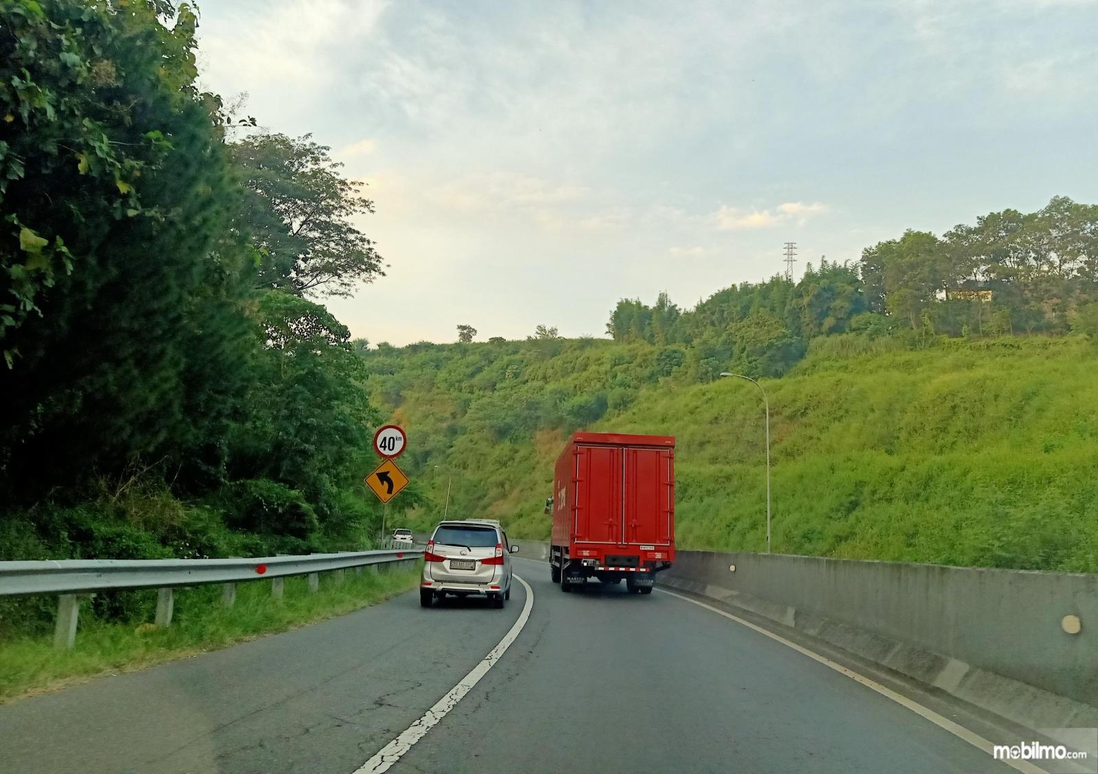 Foto menunjukkan mobil menyalip menggunakan bahu jalan tol