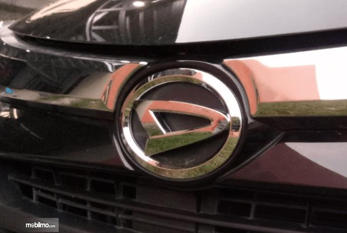 Gambar ini menunjukkan logo mobil Daihatsu warna krom pada mobil