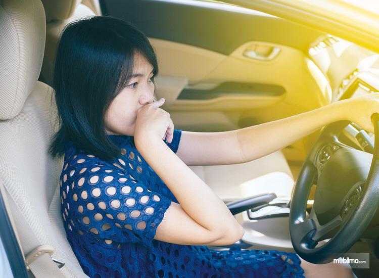 Foto menunjukkan ekspresi pengemudi yang merasa kurang nyaman dengan bau kabin mobil