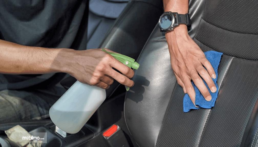 Gambar ini menunjukkan 2 buah tangan memegang kain dan tabung semprot