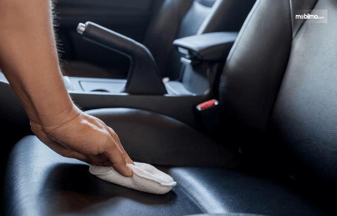 Gambar ini menunjukkan sebuah tangan memegangkain untuk membersihkan jok mobil