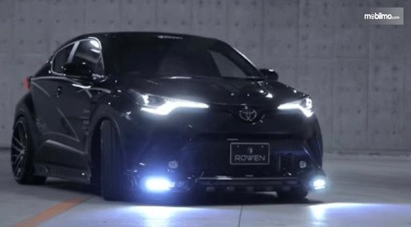 Gambar ini menunjukkan Toyota C-HR Racikan Rowen International tampak depan dengan lampu menyala