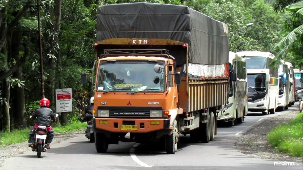 Foto menunjukkan beberapa kendaraan membuntuti truk muatan berat menunggu kesempatan mendahului