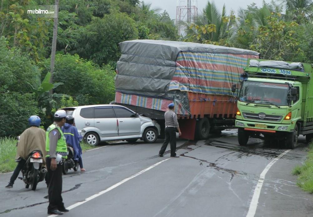 Satu unit mobil minibus tertabrak truk yang ngeloyor karena tidak kuat menanjak