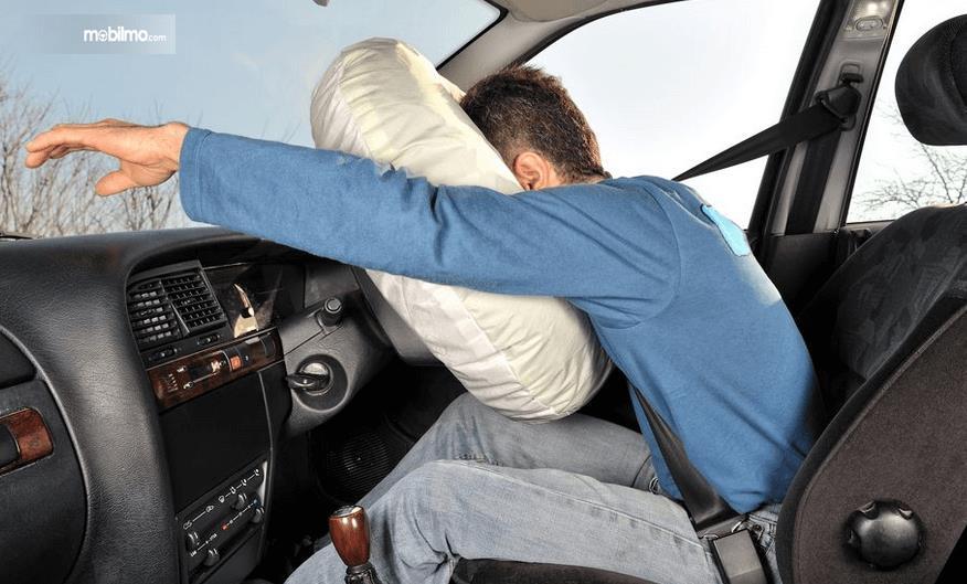 Gambar ini menunjukkan ilustrasi seorang pria menabrak airbag yang mengembang
