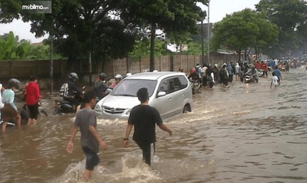 Gambar ini menunjukkan sebuah mobil melewati banjir ditonton banyak orang