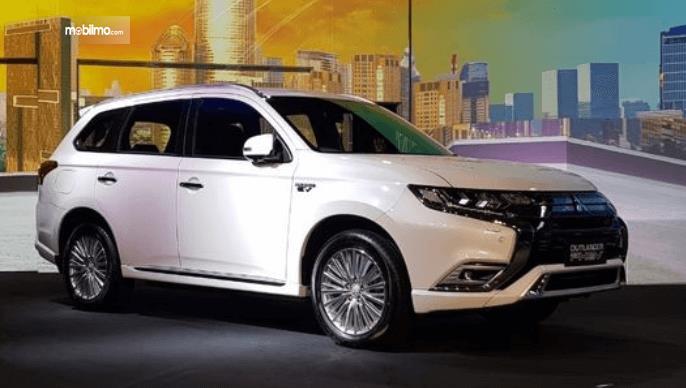 Gambar ini menunjukkan mobil Mitsubishi Outlander Edisi Plug-in Hybrid warna putih tampak samping dan depan