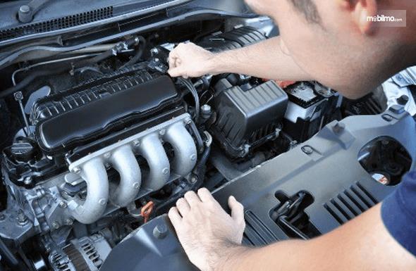 Gambar ini menunjukkan seseorang sedang memeriksa kondisi mesin mobil