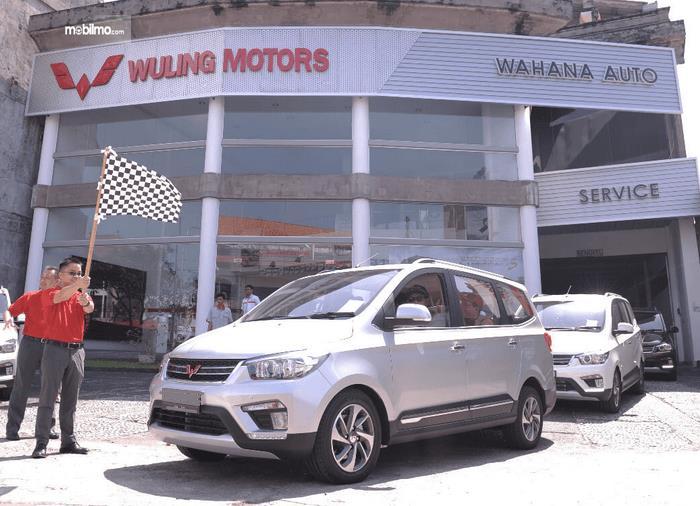 Gambar ini menunjukkan mobil Wuling dengan 2 orang berdiri di depan diler Wuling Motors