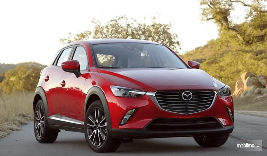 Gambar ini menunjukkan mobil Mazda CX-3 2016 warna merah tampak depan