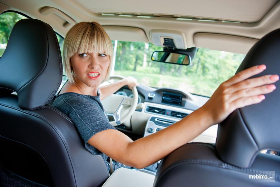 Foto pengemudi sedang melihat area belakang saat akan mundur