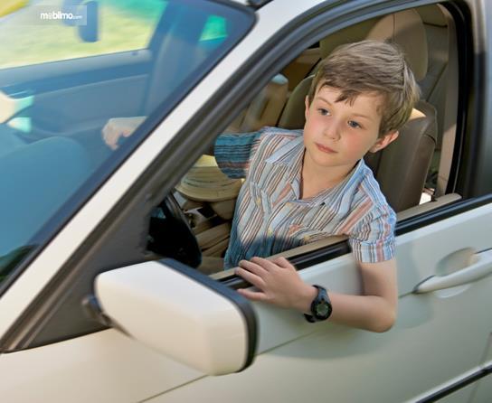 Foto menunjukkan seorang anak mengemudi mobil tanpa pendamping