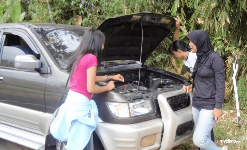 Gambar ini menunjukkan 3 wanita sedang memeriksa mesin mobil