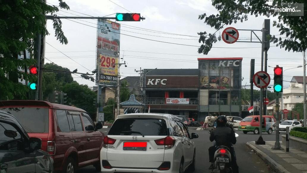 Gambar ini menunjukkan beberapa mobil sedang berhenti di lampu rambu lalu lintas