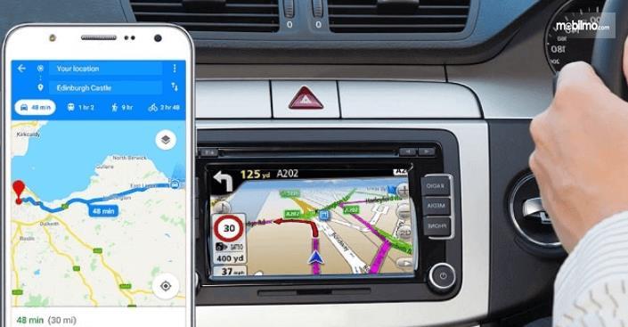 Gambar ini menunjukkan ilustrasi GPS pada mobil dan juga smartphone