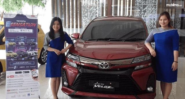 Gambar ini menunjukkan 2 orang wanita berdiri di samping mobil