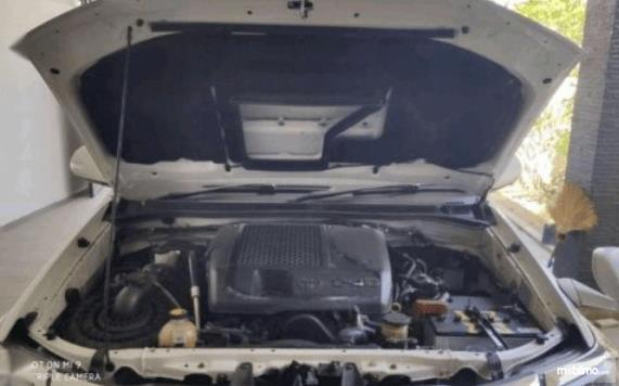 Gambar ini menunjukkan mesin mobil Toyota Fortuner 2014 dengan kap terbuka