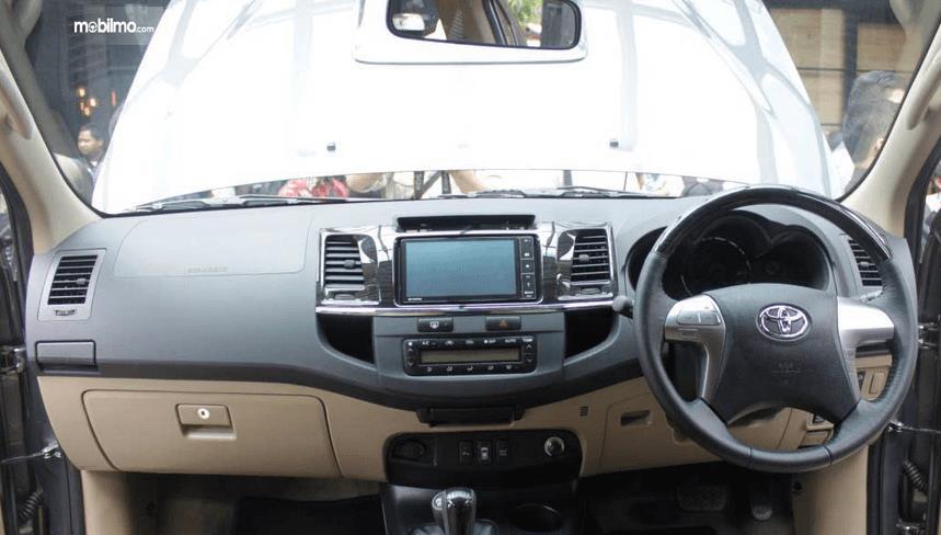 Gambar ini menunjukkan dashboard dan kemudi mobil Toyota Fortuner 2014