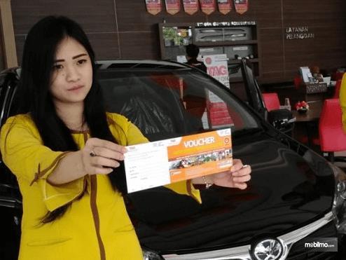 Gambar ini menunjukkan seorang sales wanita memperlihatkan voucher