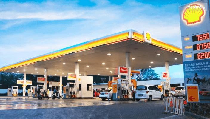 Gambar ini menunjukkan SPBU Shell dengan banyak mobil sedang isi bensin