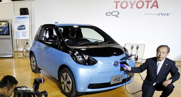 Gambar ini menunjukkan seorang pria sedang mengisi mobil listrik Toyota