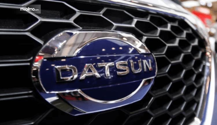 Gambar ini menunjukkan logo Datsun pada mobil di bagian depan
