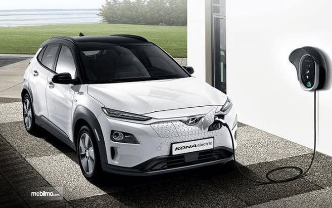 Gambar ini menunjukkan Hyundai Kona warna putih sedang diisi tenaga listriknya