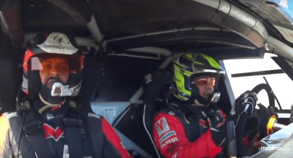 Gambar ini menunjukkan 2 pengemudi sedang berada di dalam mobil Nissan Navara Dakar 2019