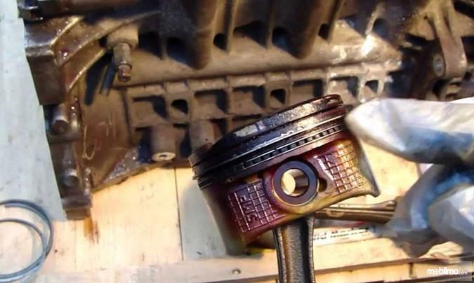 Foto menunjukkan ring piston mobil sedang diperiksa kondisinya oleh mekanik