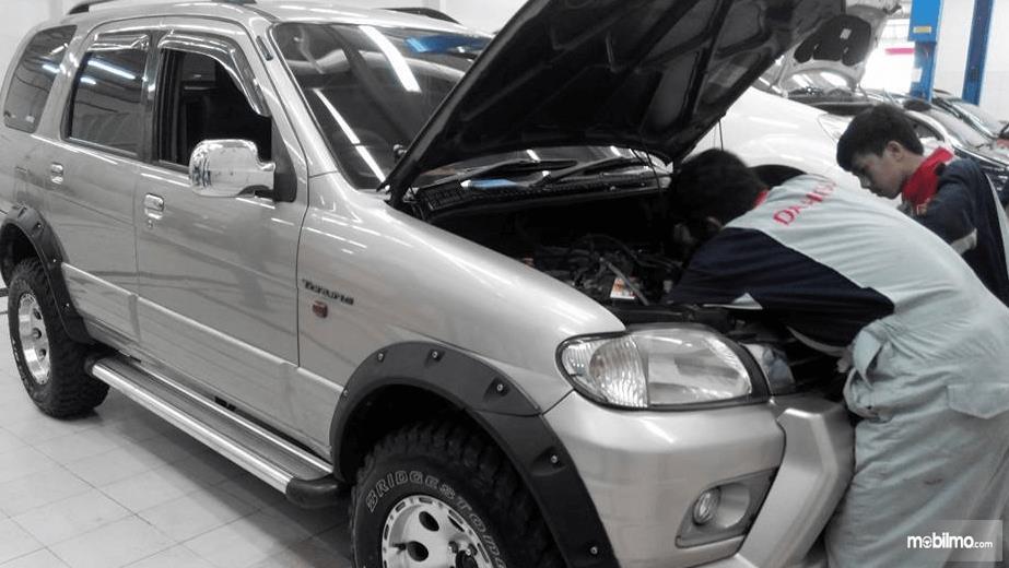 Gambar ini menunjukkan mekanik sedang memeriksa mobil Mitsubishi