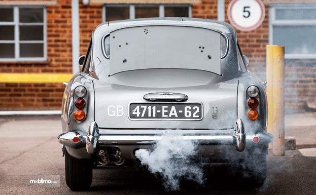 Gambar ini menunjukkan bagia belakang mobil Aston Martin DB5 dengan asap keluar dari knalpot