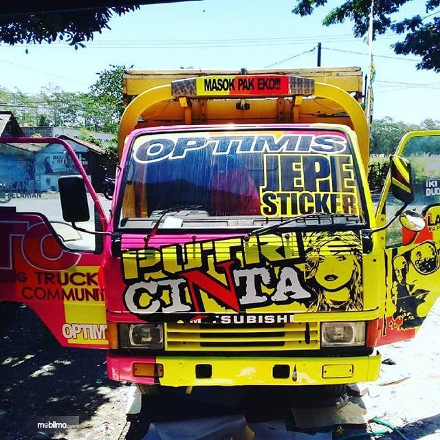 Foto menunjukkan mobil truk penuh dengan tempelan stiker