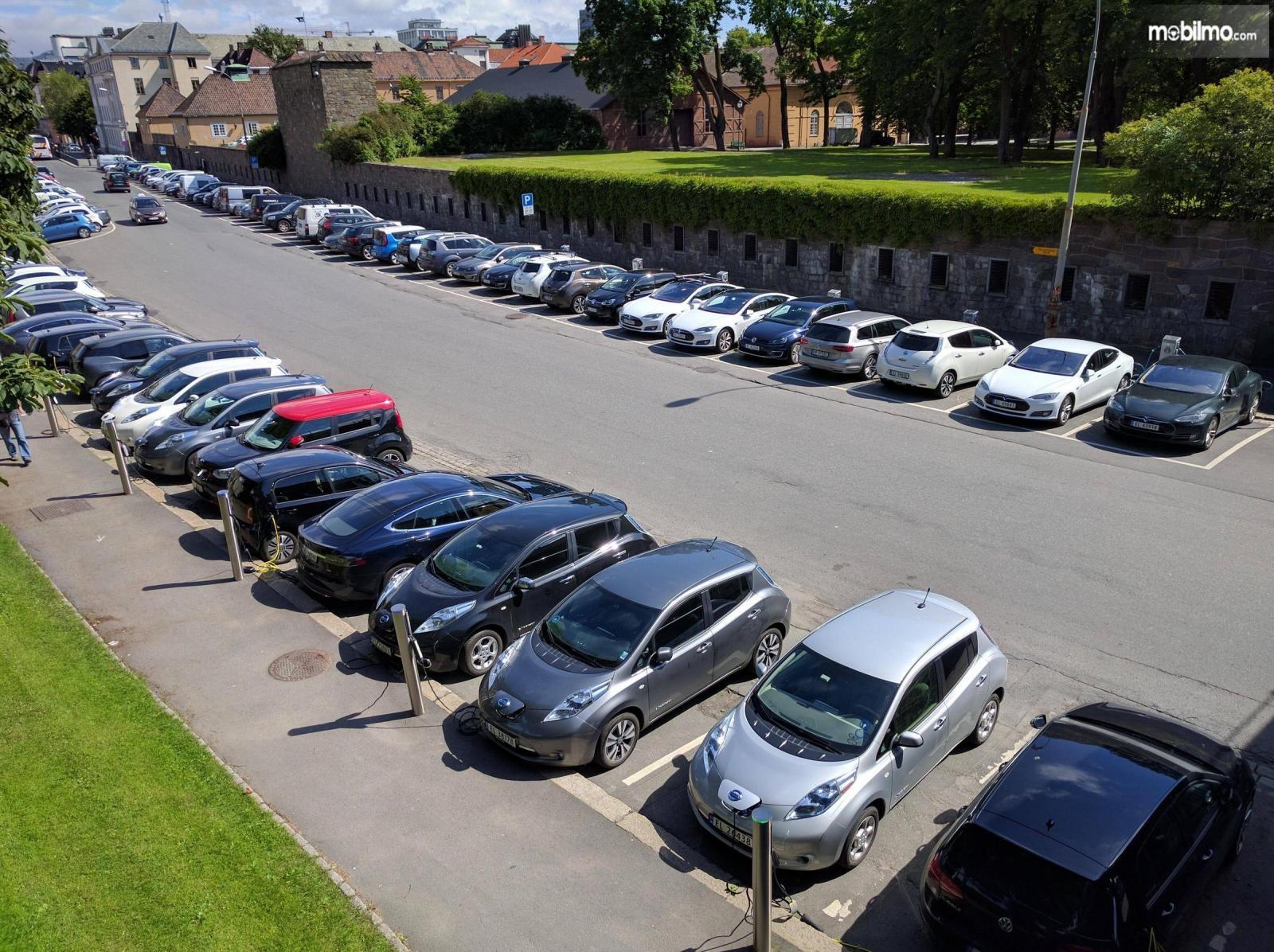 Foto puluhan mobil listrik terparkir rapi di sebuah tempat parkir di Norwegia