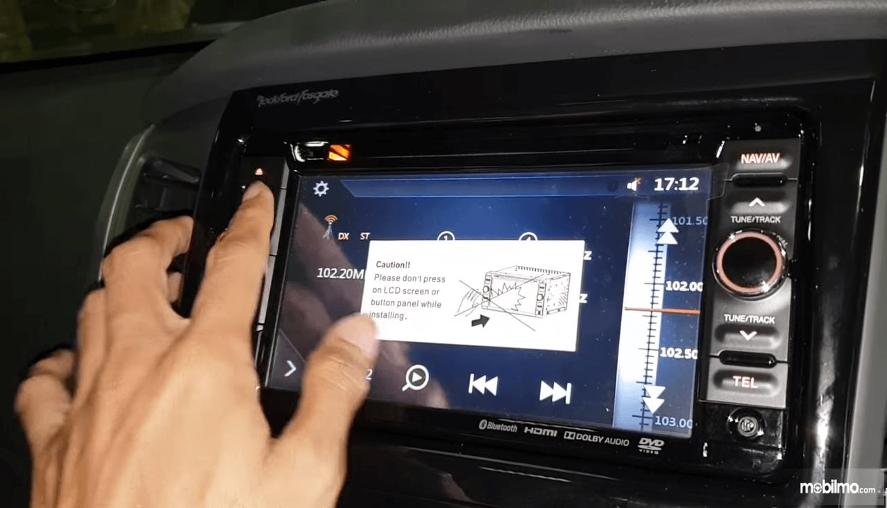 Gambar ini menunjukkan sebuah tangan sedang menekan tombol pada head unit Mitsubishi Pajero Sport Rockford Fosgate 2018