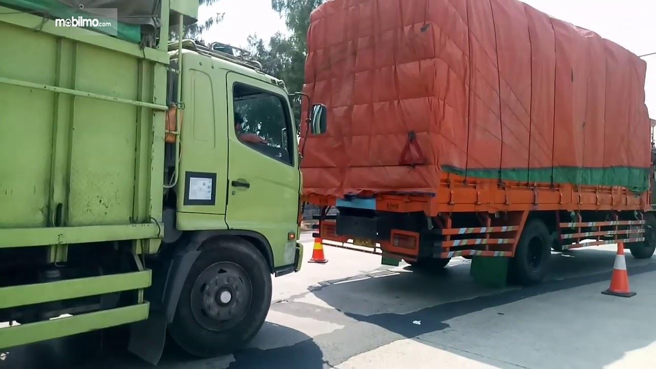 Foto menunjukkan dua unit truk kelebihan muatan