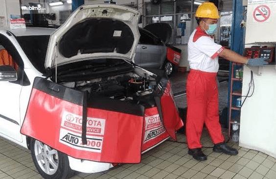 Gambar ini menunjukkan seorang mekanik dan satu mobil putih sedang dilakukan servis