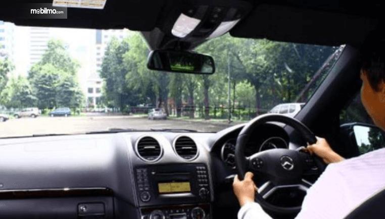 Gambar ini menunjukkan seorang pengemudi sedang melihat jalanan