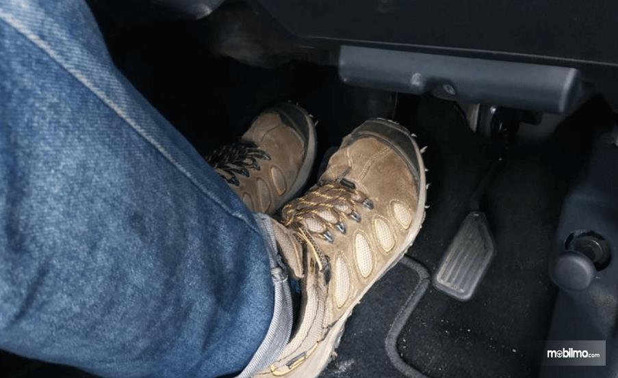 Gambar ini menunjukkan 2 kaki sedang menginjak pedal rem dan kopling