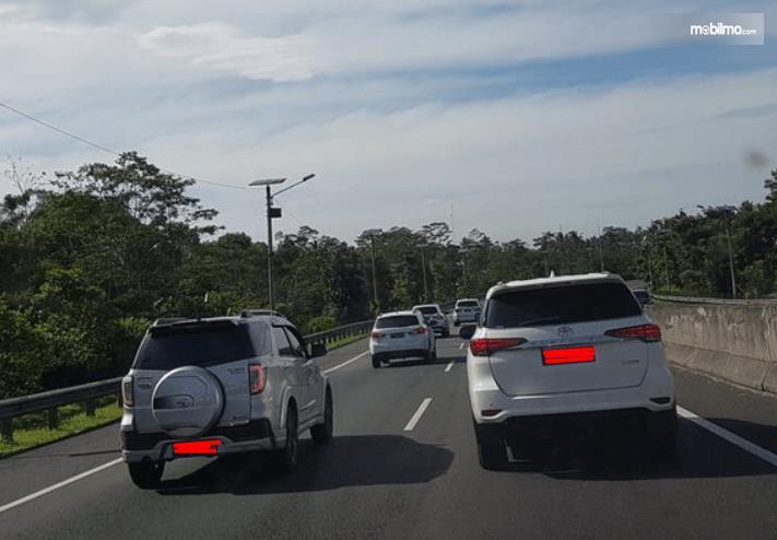 Gambar ini menunjukkan beberapa mobil sedang melaju di jalanan