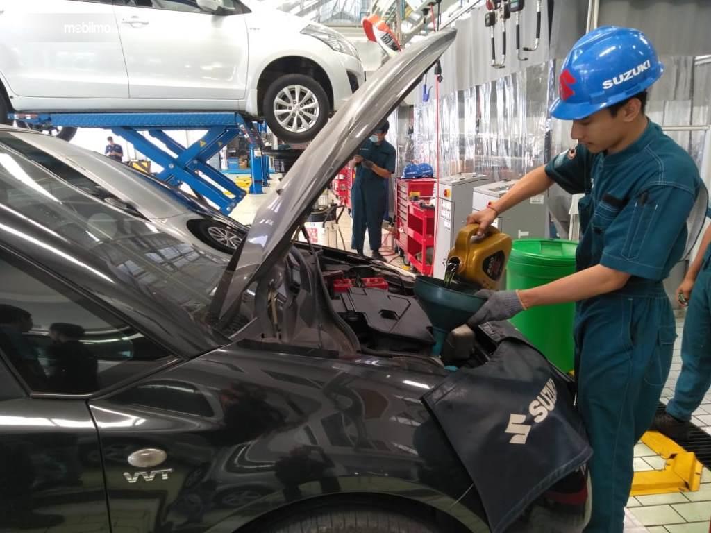Foto seorang mekanik sedang mengejakan servis mobil Suzuki di ajang Suzuki Day Singaraja - Bali