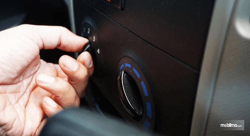 Gambar ini menunjukkan sebuah tangan sedang memegang knob pengatur AC mobil