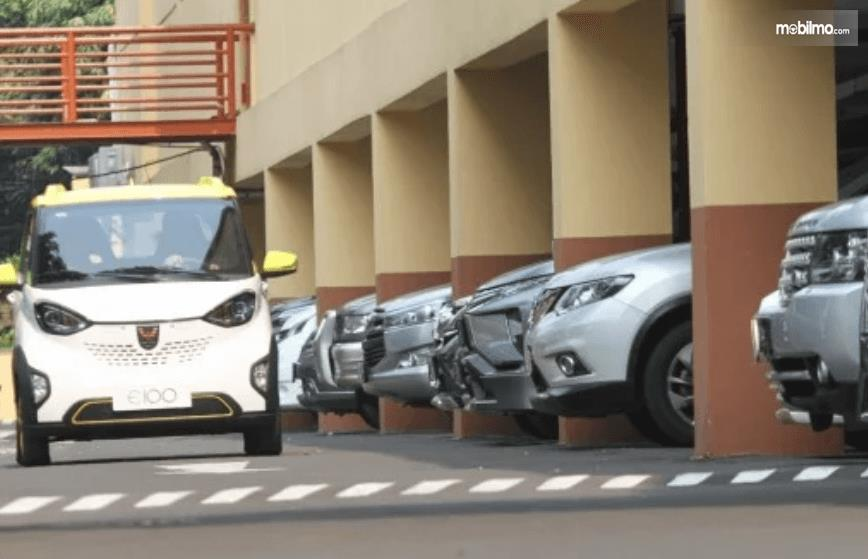 Gambar ini menunjukkan sebuah kendaraan kecil warna putih dan ujung mobil yang terparkir berjejeran