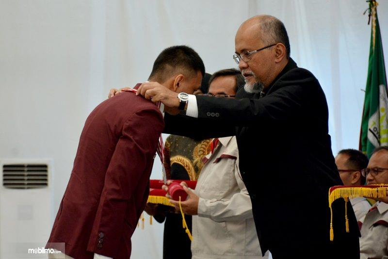 Foto Presiden Direktur TMMIN mengalungkan medali kelulusan siswa Toyota Indonesia Academy 2019