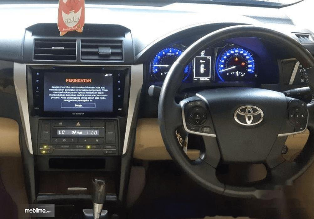 Gambar ini menunjukkan head unit dan kemudi Toyota Camry 2016