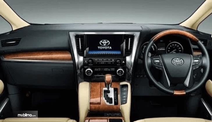 Gambar ini menunjukkan interior mobil Toyota Alphard 2015 tampak dashboard dan kemudi