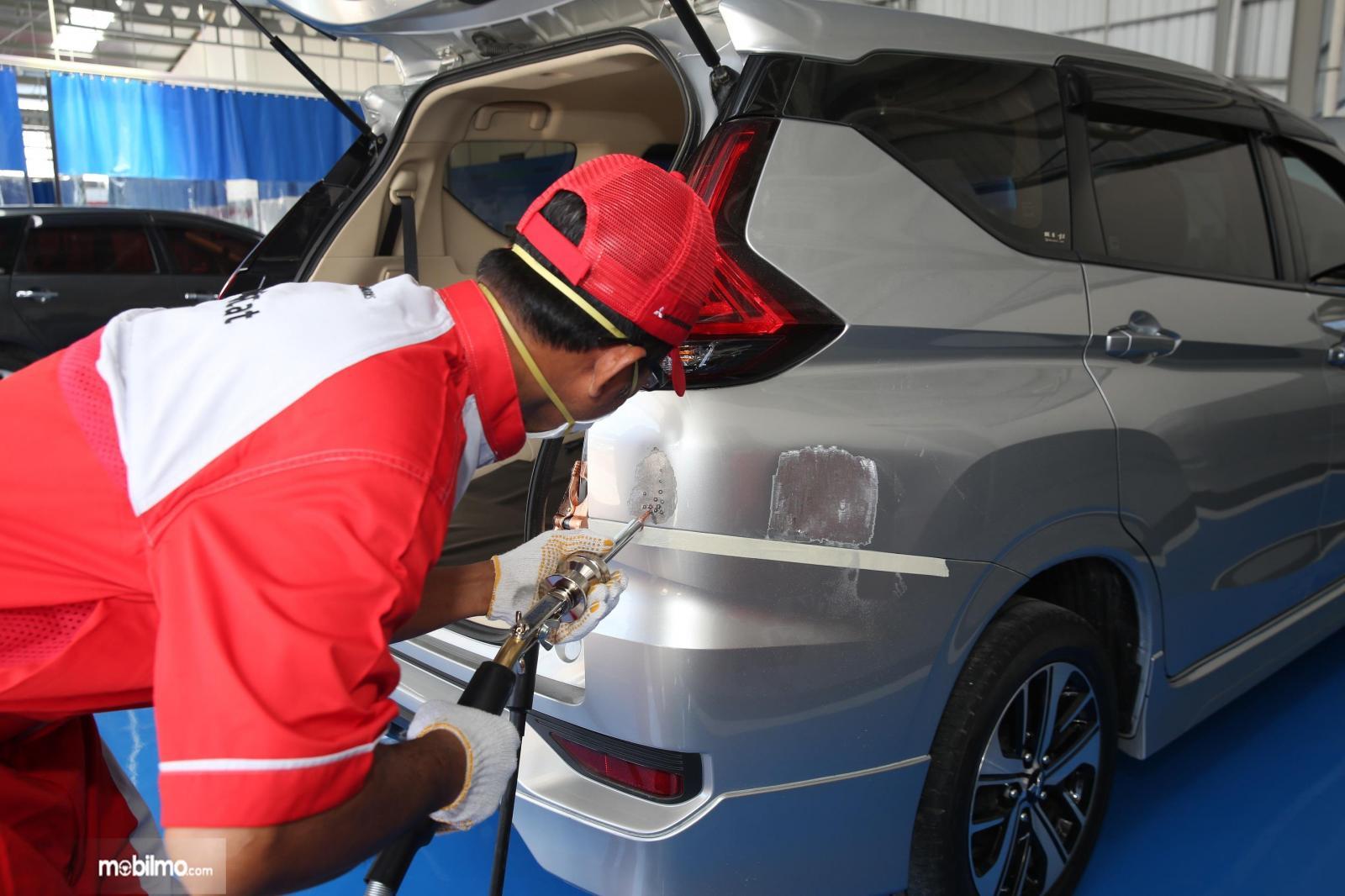 Gambar menunjukkan proses perbaikan bodi Mitsubishi Xpander di bengkel body repair