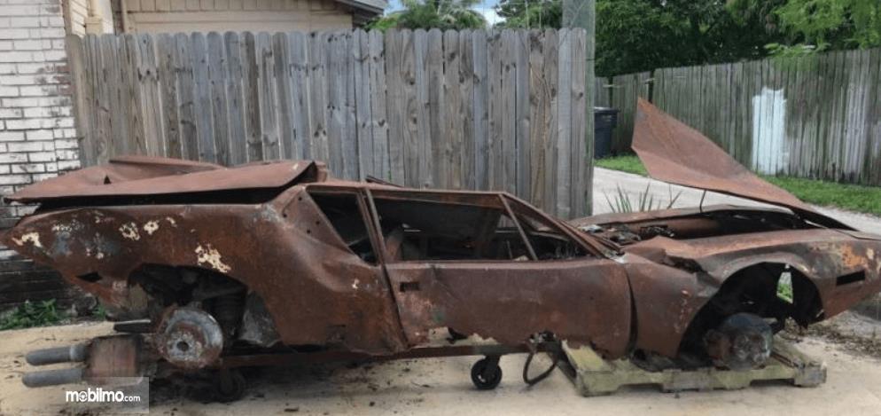 Gambar ini menunjukkan bangkai mobil bekas terbakar sampai karatan dan penyok