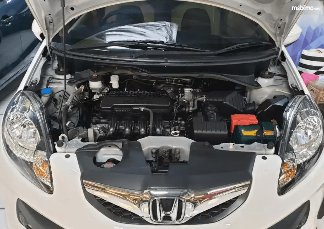 Gambar ini menunjukkan mesin mobil Honda Brio 2015 dengan kap terbuka