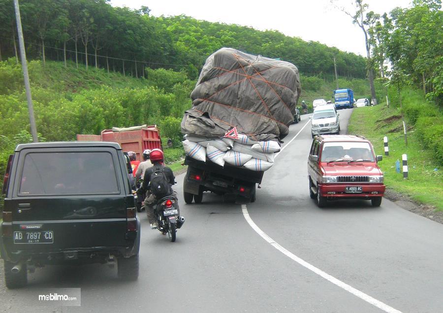 Foto Mobil miring kelebihan muatan