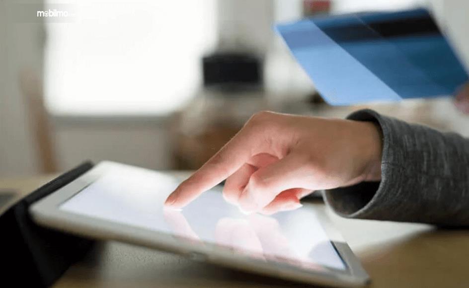 Gambar ini menunjukkan sebuah tangan sedang menekan smartphone